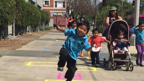Un niño juega a la rayuela en una acera de Los Ángeles, do...