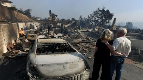 Michael y Vonea McQuillam están parados junto a su casa quemada e...