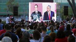 Un grupo de personas ve desde una plaza el debate realizado en el Palaci...