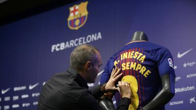 El jugador del Barcelona, Andrés Iniesta, firma una camiseta tras firmar...