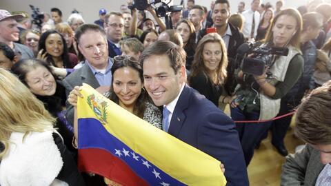 Marco Rubio posa con una simpatizante que porta una bandera de Venezuela