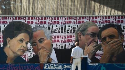 Un hombre mira a un mural en Sao Paulo en el que se ve (de izquierda a d...