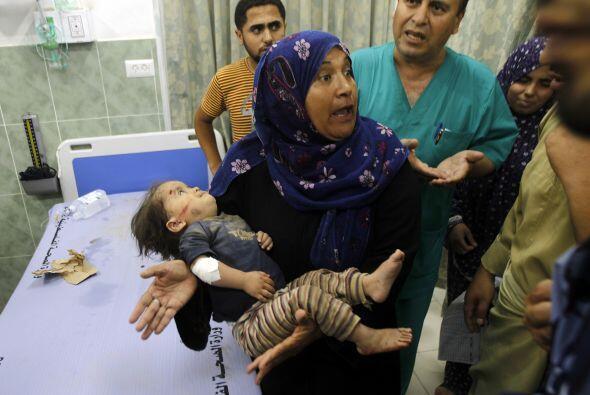 Una   mujer lleva a   un   niño herido   en   el hospital   al-...