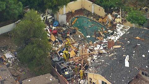 Bomberos revisan la escena sobre los escombros que dejó la explos...