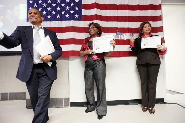 Flamantes ciudadanos de EEUU posan frente a la bandera de su país tras l...