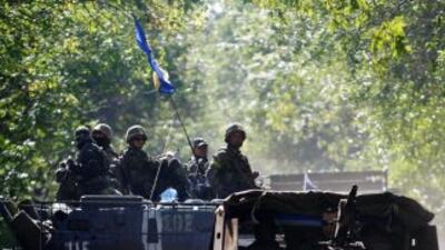 Soldados ucranianos se sientan en la parte superior de un APC patrulland...