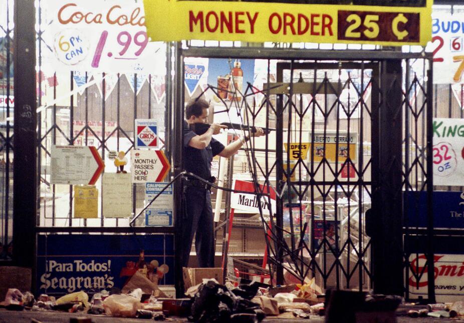 Un policía de Los Ángeles apunta a un saqueador en una tienda en la esqu...
