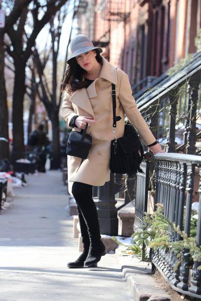 Un abrigo beige, botas envidiables combinado con un sombrerito en gris.