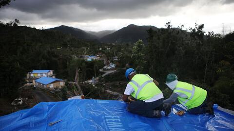 Dos contratistas colocan una lona de FEMA sobre el tejado de una casa af...