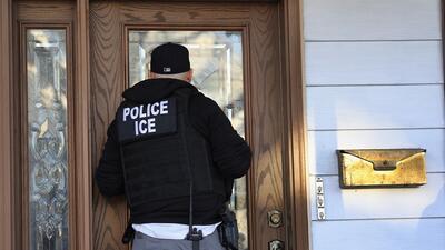 Un agente de ICE, ante la casa de un indocumentado en Nueva York.