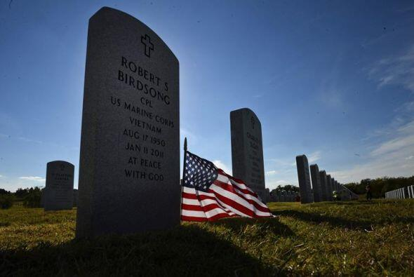 Vista de una pequeña bandera estadounidense puesta en una tumba durante...
