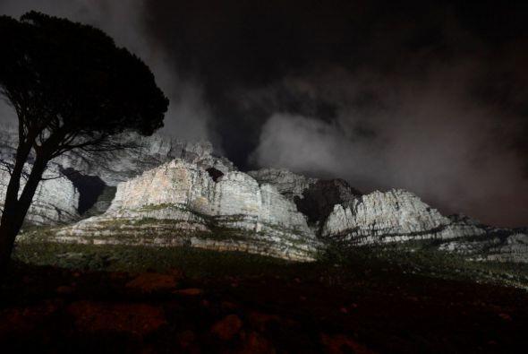Las luces brillan en la Montaña de la Mesa, junto antes de apagarse por...