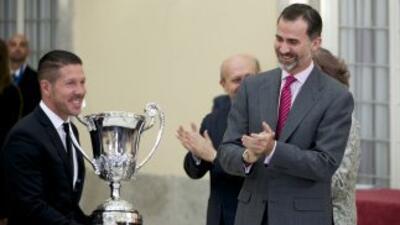 Simeone recibe el trofeo de manos del Rey de España.