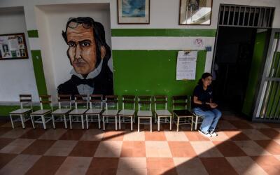 Una electoral espera a las puertas de un centro electoral vacío e...
