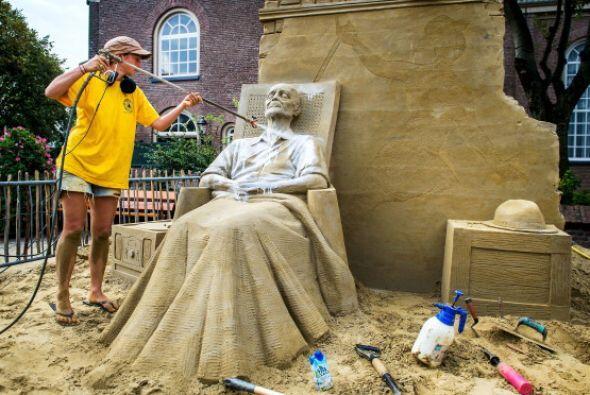 La artista británica Nicola Madera trabaja en su escultura de arena dura...