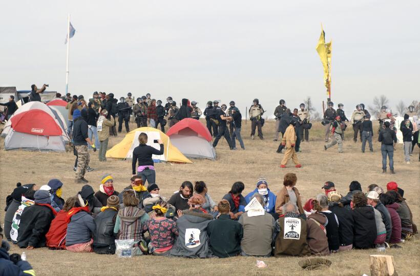Los manifestantes en círculo rodeados de agentes de seguridad en Sacred...