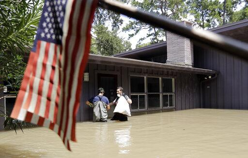 Gaston Kirby, right, and Juan Minutella leave Kirby's flooded home in th...