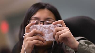 Una inmigrante de Ecuador se entretiene con su celular mientras espera a...