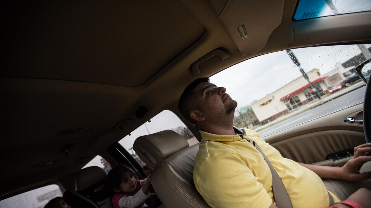 Pedro (not his real name) drives with his daughters, 8 and 4 years-old r...