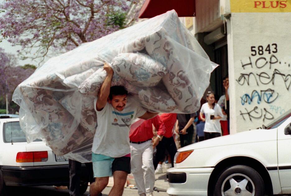 Un hispano sale de una tienda saqueada con un sofá en la espalda.