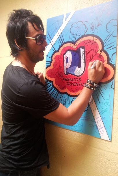 Beto Cuevas con todo y gafas firmó con mucha emoción el póster.