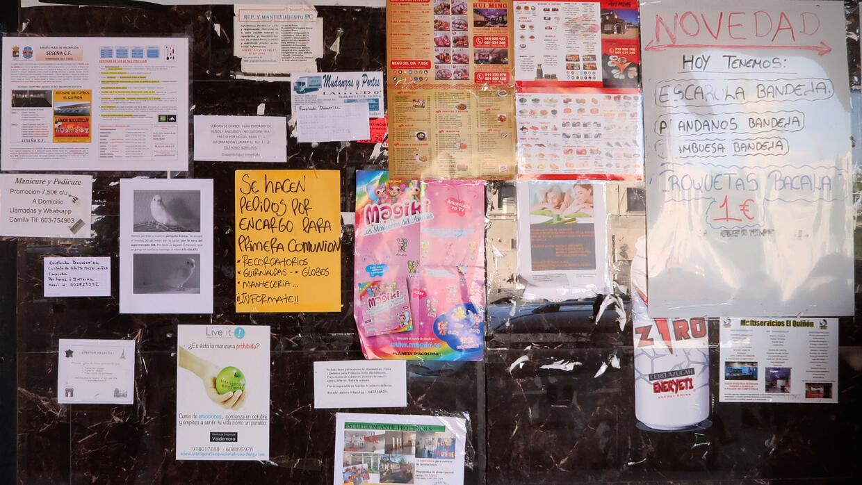 Un tablón de anuncios comunitarios en El Quiñón anuncia rutas de autobús...