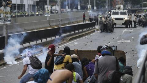Un grupo de jóvenes manifestantes se escuda tras una barrera improvisada...