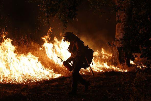 Un bombero lucha por sofocar las llamas que arden enMiddletown, Califor...