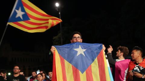 Un hombre sostiene una estelada, la bandera independentista catalana, du...
