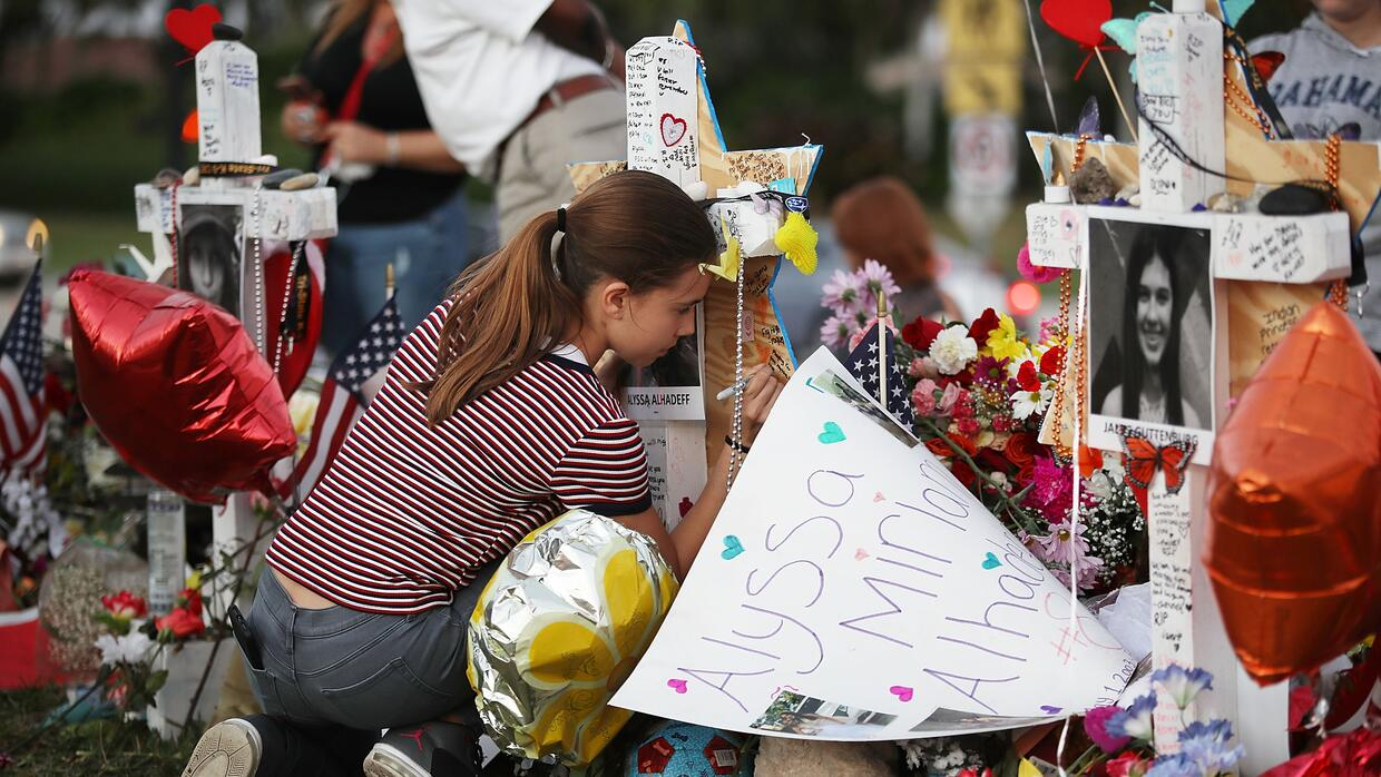 Victoria Seltzer writes on a makeshift memorial in front of Marjory Ston...