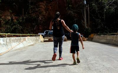 Una madre camina con su hijo por un puente roto por el huracán Ma...