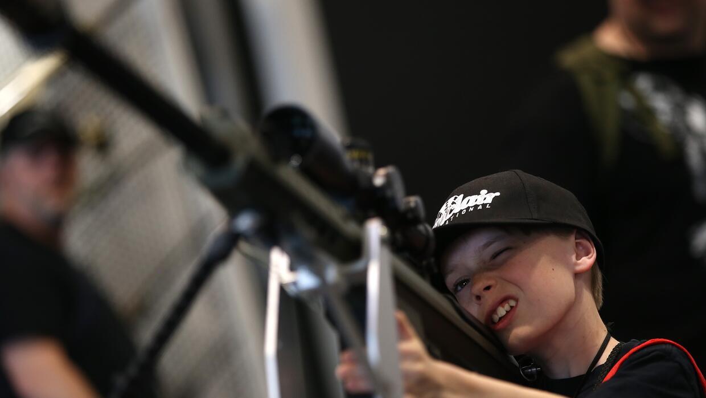 Un niño inspecciona un arma durante el encuentro anual de la Asociación...
