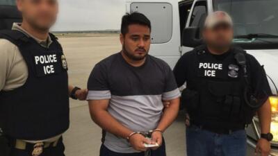Dos agentes hispanos de ICE sujetan a un fugitivo de Guatemala.