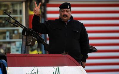 Un policía iraquí hace la señal de la victoria dura...
