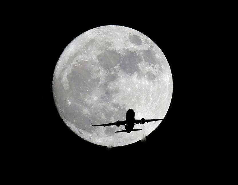 Un avión de pasajeros de American Airlines pasa frente a la Luna, visto...
