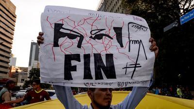 Un manifestante de la oposición levanta un cartel que lleva estampados l...