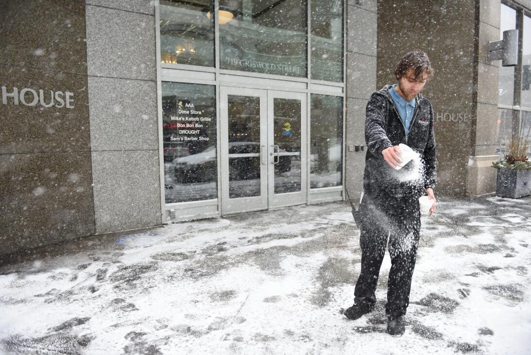 Un empleado vierte sal en la entrada de un edificio de oficinas en Detroit