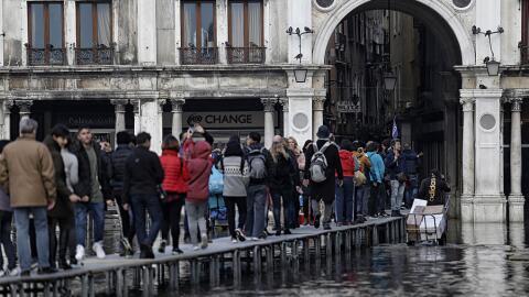 Un grupo de peatones usa la pasarela para caminar sobre el área i...