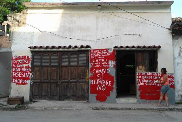 Un activista pinta nuevamente los carteles en Cuba.