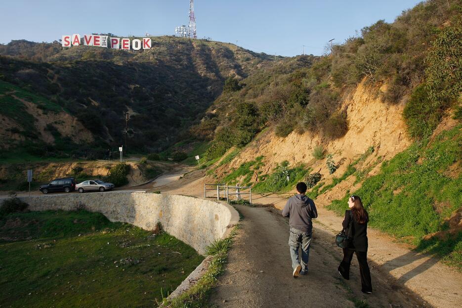 Una pareja pasea cerca de la base del letrero de Hollywood que en febrer...