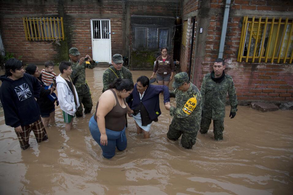 Unos soldados ayudan a una mujer a salir de su casa en un área inundada...