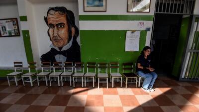 Una electoral espera a las puertas de un centro electoral vacío en Caracas.