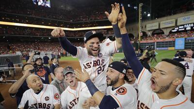 El venezolano José Altuve, de los Astros de Houston, es alzado en...