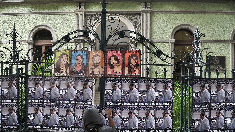 Activistas pegan carteles de periodistas muertos en Veracruz.
