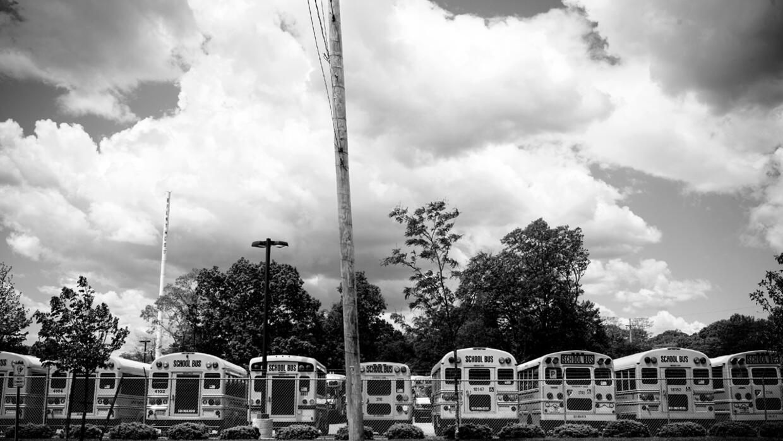 Autobuses escolares esperan cerca de la High School de Brentwood, con un...