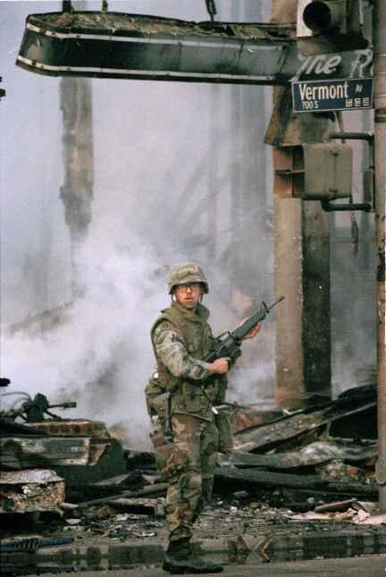 Un elemento de la Guardia Nacional vigila un incendio calcinado en la es...