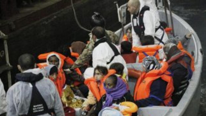 Una barca de rescate llega a un buque anfibio llevando inmigrantes resca...