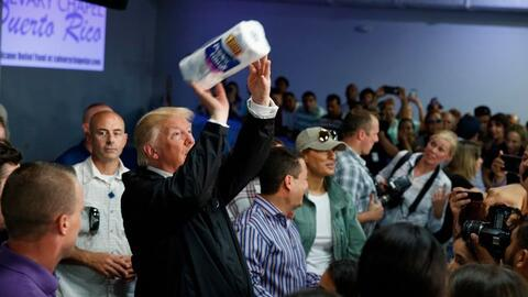 President Donald Trump tosses paper towels into a crowd as he hands out...
