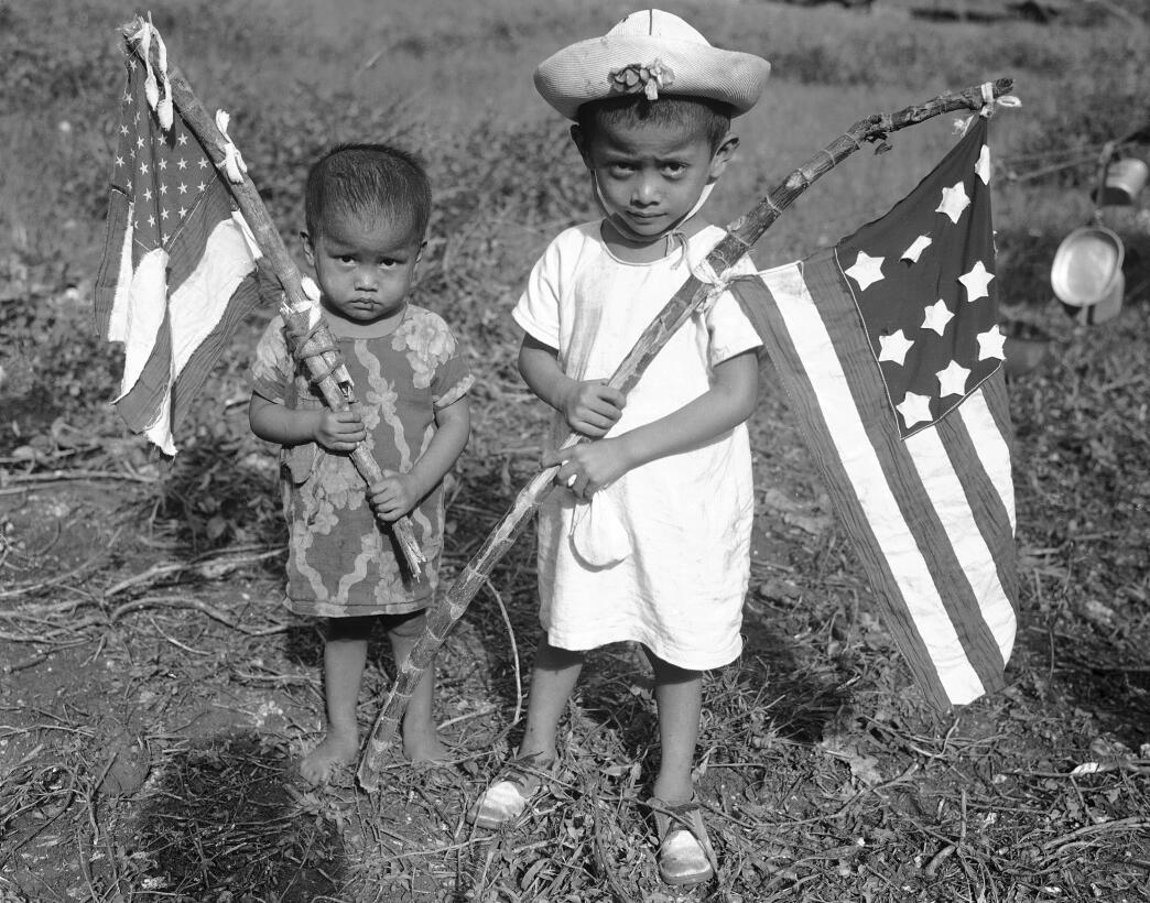 Tiny natives of Guam hold home-made American flags made by their mothers...