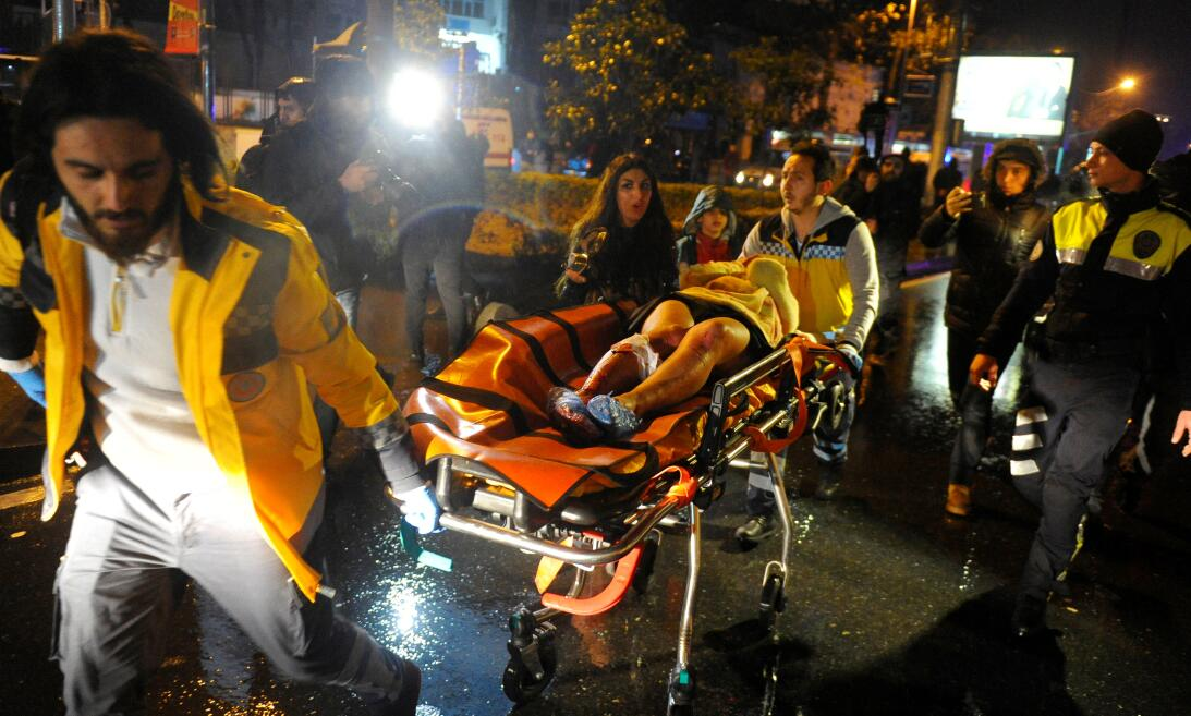 Una mujer herida es llevada a una ambulancia desde la discoteca donde se...
